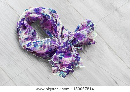 Crumpled colorful silk kerchief on wooden background