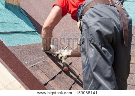 Roofer builder worker use a hammer for installing roofing shingles