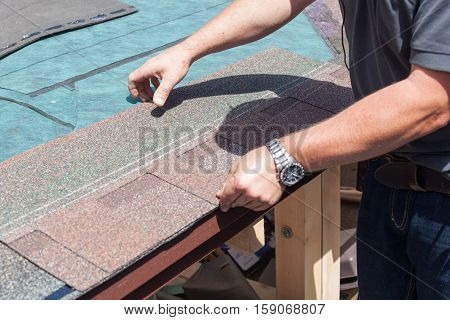 Roofer builder worker installing roof shingles close up