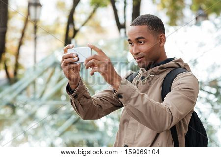 Photo of young dark skinned man photographing outdoors with his cellphone. Looking at phone.