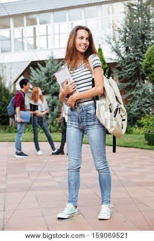 Smiling pretty young woman student with backpack walking outdoors