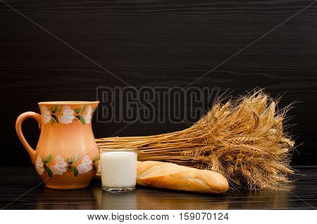 Jug glass of milk a loaf and a sheaf of ears on a black background