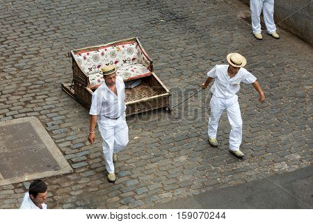 FUNCHAL, MADEIRA, SPAIN - SEPTEMBER 2, 2016: Toboggan riders moving traditional cane sledge downhill on the streets of Funchal. Monte park Madeira island Portugal