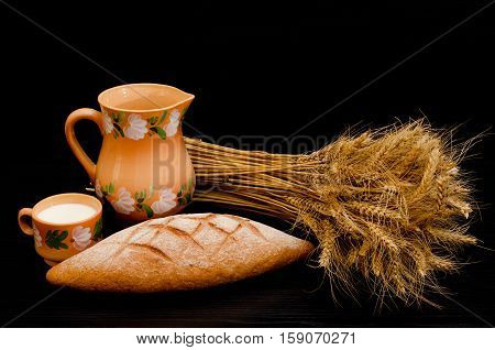 Jug a cup of milk a loaf and a sheaf of ears on a black background