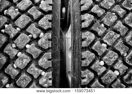 Close up of rocks stuck in industrial size truck tire treads