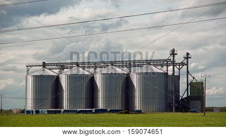 A Collection Of Four Shiny New Grain Bins Against A Twilight Sky