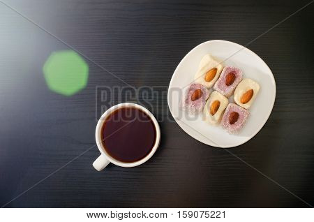 Mug of tea and Turkish Delight with almonds on a saucer solar flare top view black background