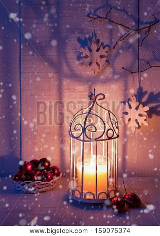 Christmas decorations and lantern at the evening . Focus on the wick candle
