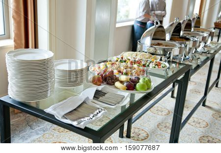 table set for a feast of fruit salads stacks of white plates cutlery and waiters in the background