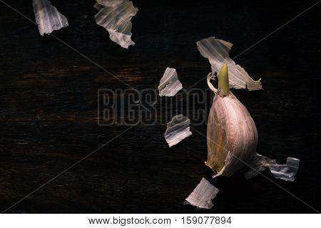 Single Clove Of Garlic On Dark Wooden Board