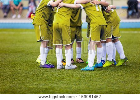 Young football soccer players in yellow sportswear. Young sports team on pitch. Pep talk before the final match. Soccer school tournament. Children on sports field.