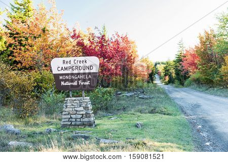 Public sign of Red Creek Campground in Monongahela National Forest with road and autumn trees
