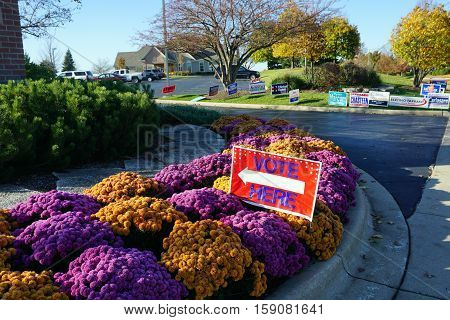 JOLIET, ILLINOIS / UNITED STATES - NOVEMBER 8, 2016: A sign, in a chrysanthemum garden, indicates the direction to the place to vote, outside the Wesmere Country Club Clubhouse, which serves as a polling place on election day.