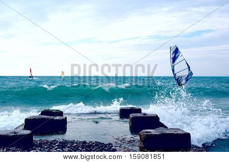 Group of windsurfers on boards in wavy sea with pier on coast. Lifestyle and sport completition concept. Group of people. Fun and leisure activity.