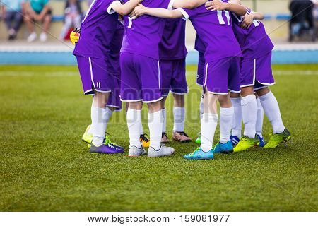 Young football soccer players in purple sportswear. Young sports team on pitch. Pep talk before the final match. Soccer school tournament. Children on sports field.