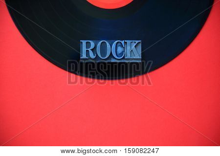 The word rock in metal type on a black vinyl record on a red background with copy space