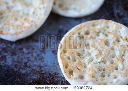 English muffin halves closeup toasted on a worn baking pan