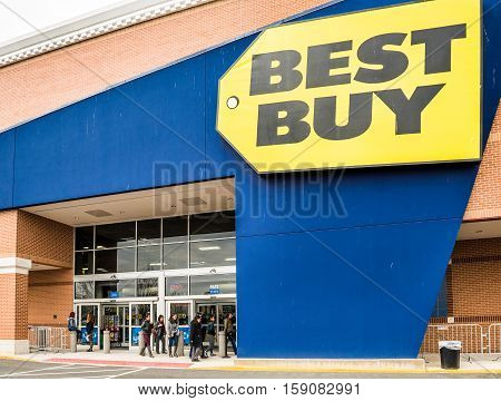 Fairfax, USA - November 25, 2016: Best Buy store facade with huge sign in downtown in Virginia city with people walking around entrance
