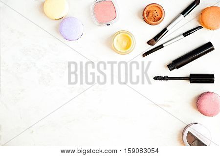 Flat lay of fashion lady products on a marble background. Macaroons and makeup products mascara blushes lip butter. Copy space for text