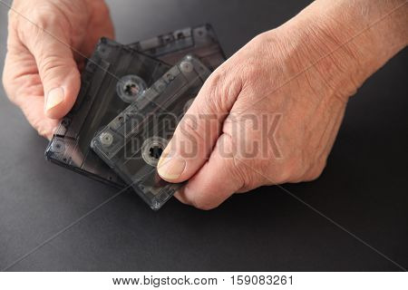 Senior man with three old cassette tapes on a dark background with copy space