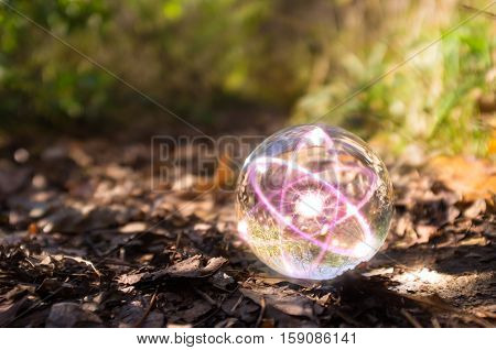 Magic crystal ball atom on forest floor for autumn fantasy imagery