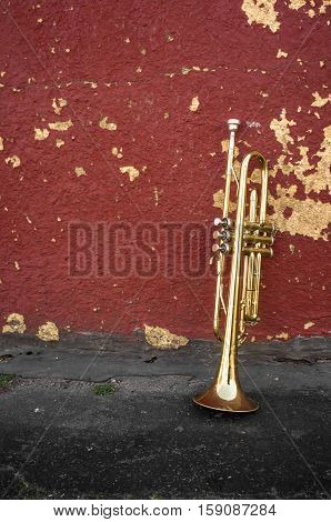 Old worn trumpet stands alone against a grungy pealing red wall