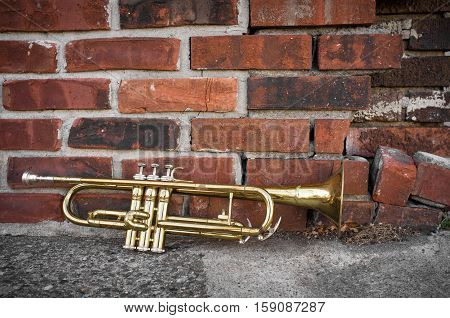 Old worn trumpet stands alone against a grungy brick wall