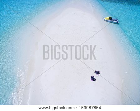 Landscape seascape aerial view over  Maldives Male Atoll sandbank island. Jet ski and life vests at the white sandy beach