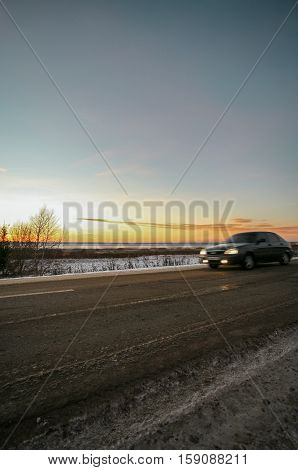 winter road at the snow-covered coast of the lake against the background of a bright decline.