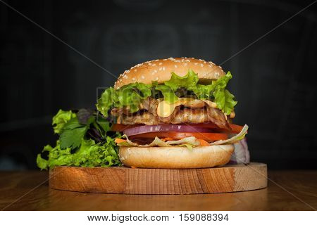 A delicious burger with bacon with lettuce on a wooden board on a dark background. Photo causing appetite. The concept of fast food but delicious food unwholesome.