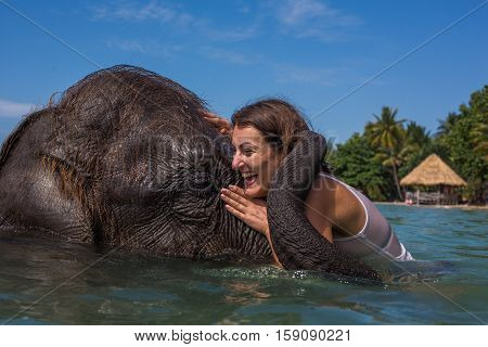 Girl swims with the elephant in the blue sea-ocean in Thailand