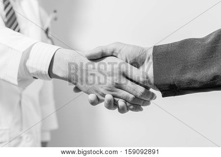 doctor and her lawyer shaking hands black and white.doctor's hands holding patient's hand for encouragement and empathy. Doctor concept. Doctor man. Doctor support. Doctor talk. Doctor trust. Doctor shake. Doctor waiting