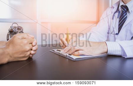 Close-up Of Male Doctor Filling The Medical Form. Doctor write. Doctor writtng. Clinic doctor. Doctor man. Doctor writting paper. Doctor workplace.