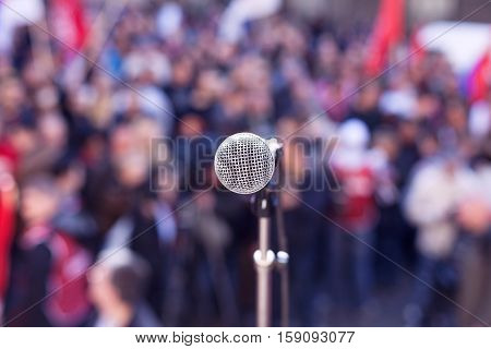 Street protest. Political rally. Microphone in focus against blurred crowd.