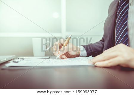 Business man signing a contract . Close-up photo vintage tone. Business man. Business room. Business working. Business writting. Business reading.