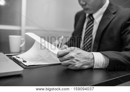 Business man signing a contract . Close-up photo black and white. Business room. Business man. Business writting. Business reading. Business office. Business working.