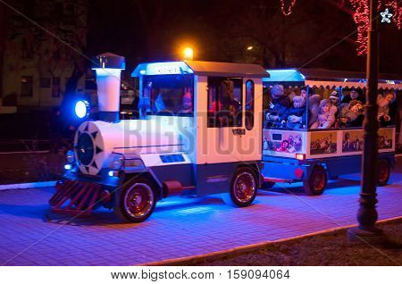 People ride by childish train at an illuminated park. An entertainment for children and their parents. Potemkin square - Kherson Ukraine Christmas - January 07, 2014.