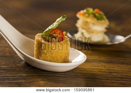 Polenta cups with shredded ragu and cabbage chips in a spoon. Taste gastronomy finger food poster