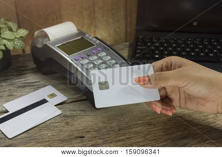 Hand Holding Credit Card Terminal Or Edc On Cashier Table In The Store , Clock,coins In The Bottle,c