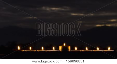 Menorah with the glitter lights of candles. Selective focus and night cloudscape as background