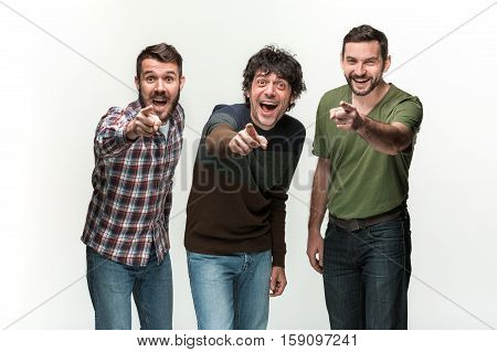The young three men are smiling, looking and pointing at camera, standing on white studio background