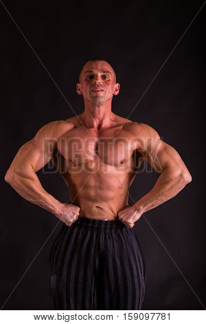 very muscular handsome athletic man on black background