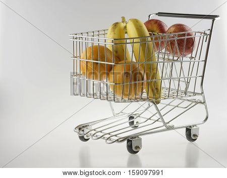 mini shopping cart as a fruit basket or grocery cart holding oranges apples and bananas in front of a gradient white background with reflection viewed from front-left