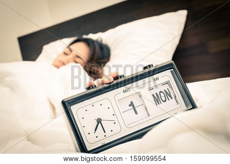 Sleepy Asian woman stopping alarm clock in morning in bed room before wake up