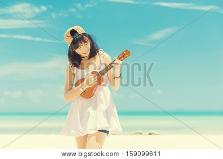 Women playing ukulele at the beach. Asia girl at beach from Thailand. Beautiful young woman playing ukulele at sea on blue sky. vintage tone