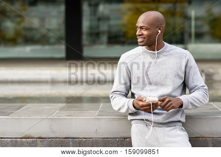 Attractive Black Man Listening To Music With Headphones In Urban Background.