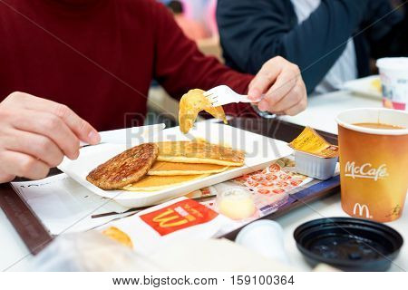 HONG KONG - CIRCA NOVEMBER, 2016: a man eat breakfast at a McDonald's restaurant in Hong Kong. McDonald's, or simply McD, is an American hamburger and fast food restaurant chain.