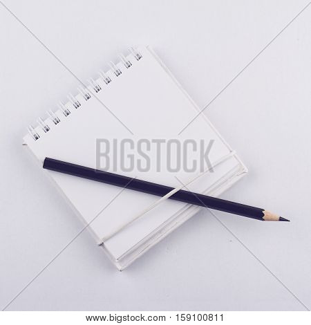 Front view of a white paper notebook with metallic spiral and a black pen