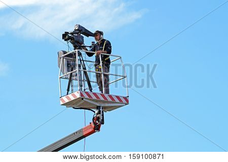 MILAN , ITALY -10 November 2015 : Cameraman working on an aerial work platform.