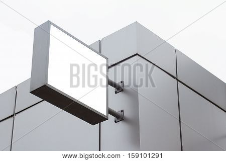 Horizontal front view of empty square white signage on a building with modern metallic plates